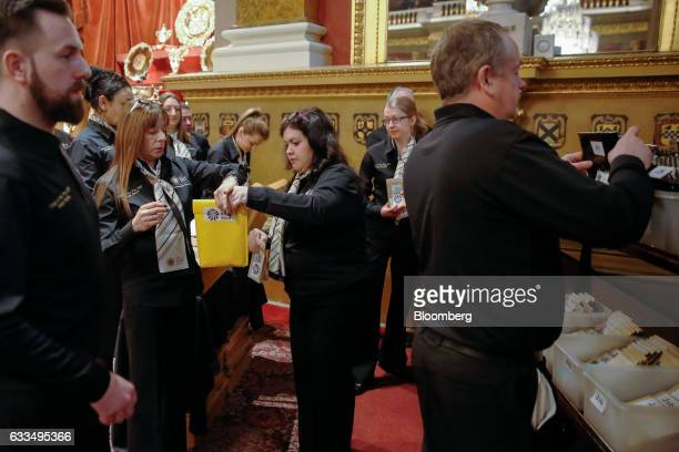 Employees of The Royal Mint Ltd prepare envelopes containing a randomized selection of coins to be sorted counted and weighed before the opening of...