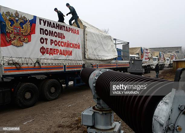 Employees of the Russian Emergency Ministry remove a tarpaulin that reads 'Humanitarian assistance from Russian Federation' as they unload lorries...