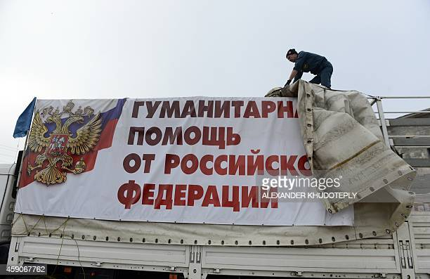 Employees of the Russian Emergency Ministry removes a tarpaulin that reads 'Humanitarian assistance from Russian Federation' as they unload lorries...