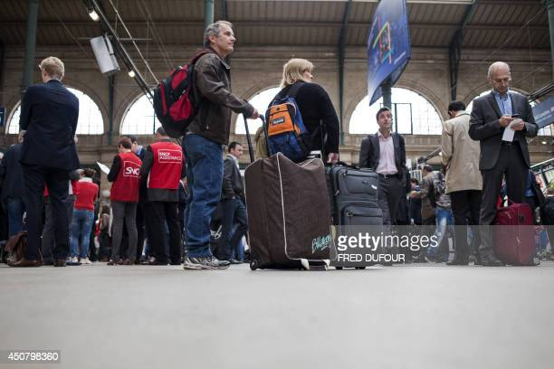 Employees of the SNCF assistance service assist commuters as people wait at Gare du Nord train station in Paris on June 18 during a national strike...