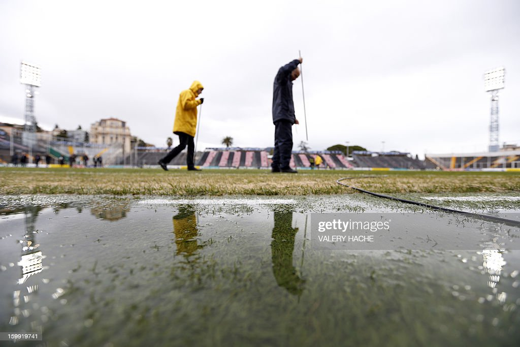Employees of the stadium examines the field damaged by heavy rains some hours before the French Cup football match Nice vs Nancy, on January 23, 2013 at the Ray stadium in Nice. The local authority in charge of wheather forecast will decide if the match takes place.