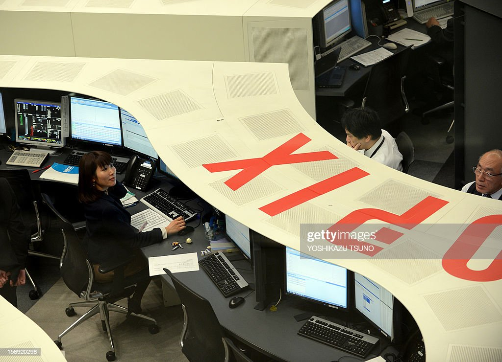 Employees of the Tokyo Stock Exchange work on the first trading day of the year at the Tokyo Stock Exchange on January 4, 2013 after the New Year's holidays. Japanese share prices rose 270.92 points to close at 10,666.10 points at the morning session of the Tokyo Stock Exchange, as the yen tumbled on relief over a US deal to avert the 'fiscal cliff' of tax hikes and huge spending cuts. AFP PHOTO / Yoshikazu TSUNO