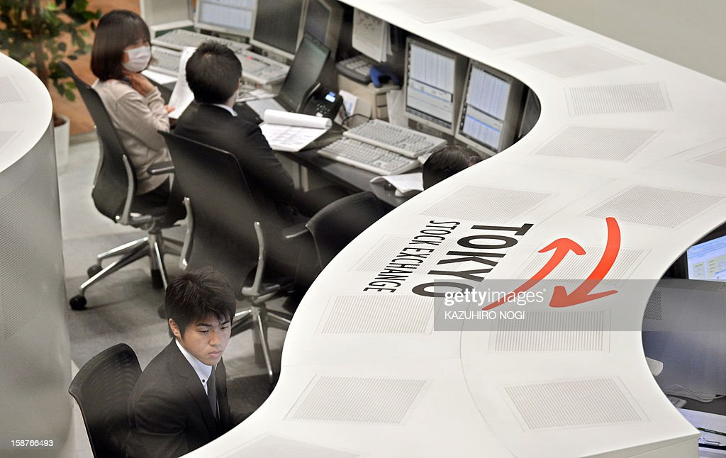Employees of the Tokyo Stock Exchange work on the last trading day of 2012 at the Tokyo Stock Exchange in Tokyo on December 28, 2012. The Nikkei ended the last trading day of the year up 0.70 percent, or 72.20 points, closing at 10,395.18, its best finish since Japan's quake-tsunami disaster in 2011, and up 22.9 percent over the past year. AFP PHOTO / KAZUHIRO NOGI