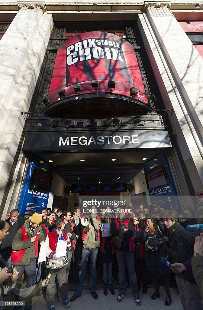 Employees of the Virgin Megastore demonstrate against job cuts in front of the shop on the Champs-Elysees avenue, on December 29, 2012 in Paris.