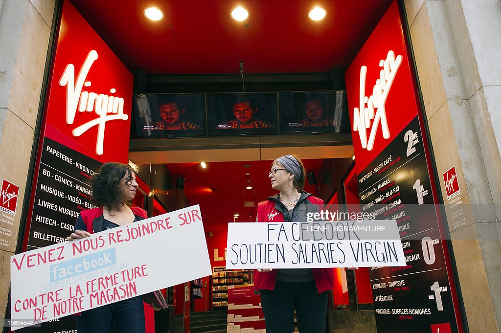 Employees of the Virgin Megastore on the Champs-Elysees avenue hold signs reading 'Come join us on Facebook in our struggle against our store's closing' and 'Facebook supports workers at Virgin' as they demonstrate against planned job cuts, at the store's entrance, on January 4, 2013, in Paris. The Virgin Megastore chain, which currently employs 1000 workers in France, is planning to file for bankruptcy and is convening an extraordinary board meeting to this effect on January 7. Originally started by Richard Branson, the British billionaire and chairman of the Virgin Group, the Virgin Megastores were bought by the French Lagardere group in 2001. AFP PHOTO / LIONEL BONAVENTURE