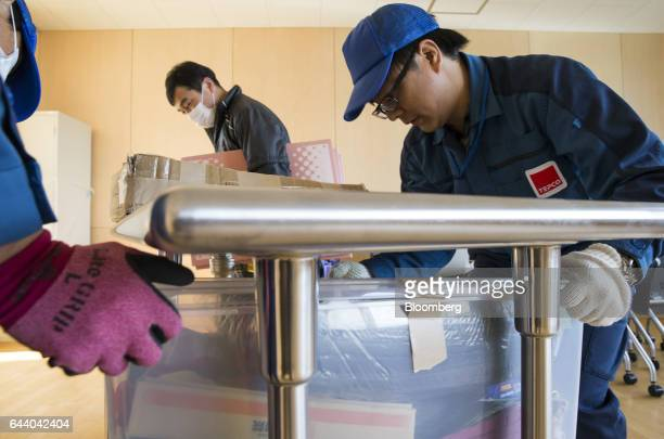 Employees of Tokyo Electric Power Co carry boxes into a classroom at the Narahamachi elementary school during preparations for the school's reopening...