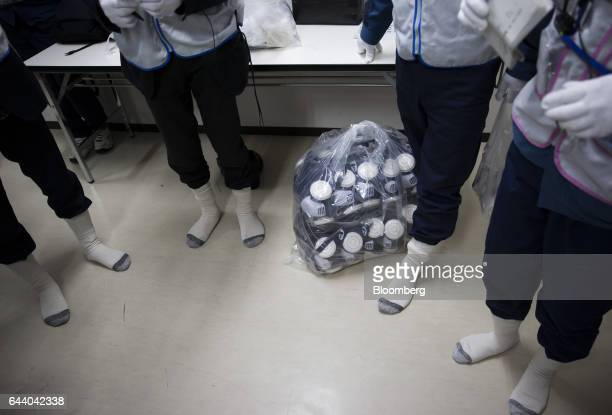 Employees of Tokyo Electric Power Co prepare their clothing before guiding members of the media on a tour of the company's Fukushima Daiichi nuclear...