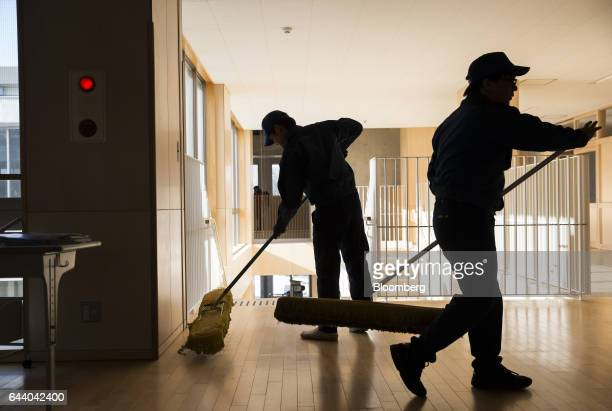 Employees of Tokyo Electric Power Co sweep a corridor at the Narahamachi elementary school during preparations for the school's reopening in April in...