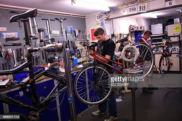 Employees of Woodrup Cycles repair customers' bikes in their workshop in Leeds Northern England on March 31 2015 Woodrup cycles was founded by...