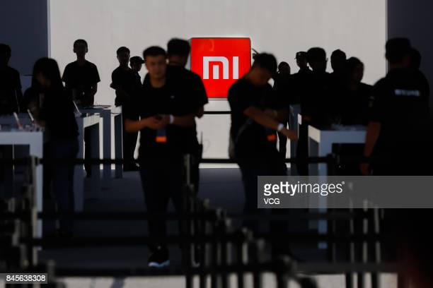 Employees of Xiaomi Corp work at a display area for new products during a launch event at Beijing University of Technology on September 11 2017 in...