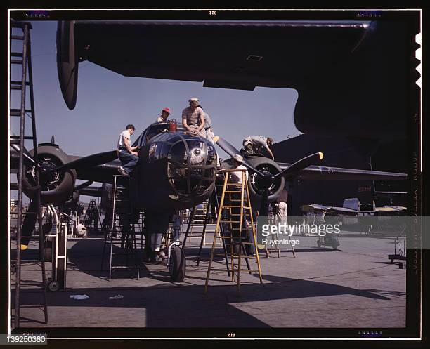 Employees on the Sunshine assembly line at North American's plant put the finishing touches on another B25 bomber Inglewood California 1942