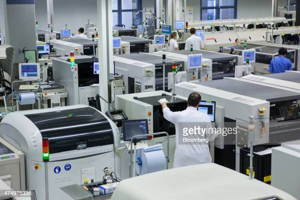 Employees operate machinery including 3D printing devices as they manufacture automotive sensors inside Continental AG's powertrain division factory...