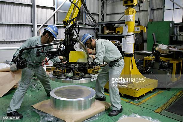 Employees operate machinery to stack coils of aluminum strip for packaging at the Tokiwa Koutai Co processing plant in Tokyo Japan on Friday Aug 7...