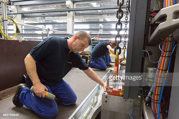 Employees oversee a winch as they lift a section of a Heidelberg industrial printing press in the Heidelberger Druckmaschinen AG manufacturing hall...