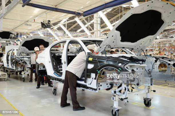 Employees overseen by a BMW launch trainer assemble a BMW 530i sedan on the production line at a PT Gaya Motor plant in Jakarta Indonesia on...