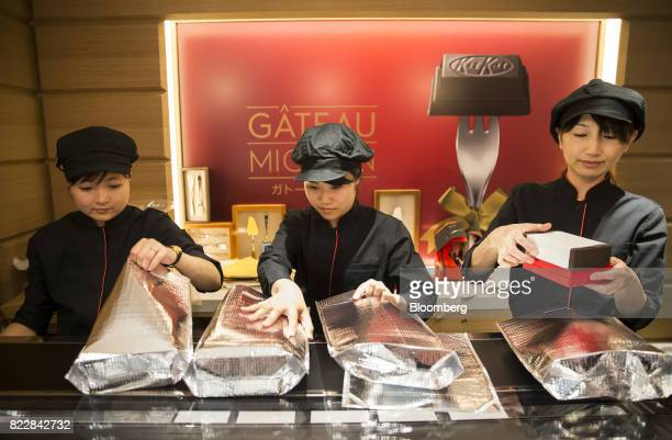 Employees pack boxes of confectionery in thermal bags in front of an advertisement for the Gateau Mignon KitKat during a media preview of the KitKat...