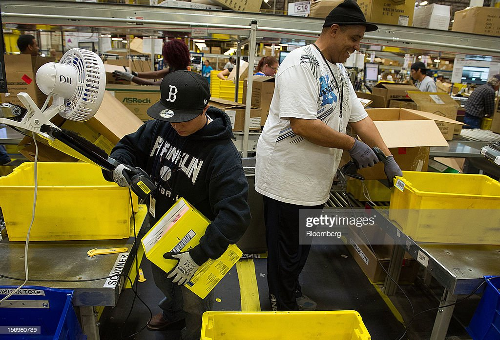 Employees pack items to be shipped from the Amazon.com Inc. distribution center in Phoenix, Arizona, U.S. on Monday, Nov. 26, 2012. U.S. retailers are extending deals into Cyber Monday and beyond to try to sustain a 13 percent gain in Thanksgiving weekend sales. Photographer: David Paul Morris/Bloomberg via Getty Images