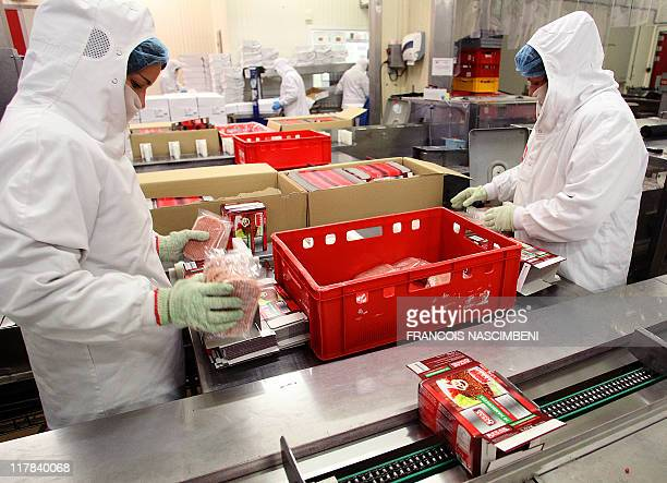 Employees pack on June 16 the frozen ground beef on the production line at the French company SEB in SaintDizier eastern France Six children are...