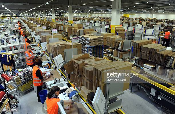 Employees pack parcels at the logistics centre of Amazon in Bad Hersfeld central Germany on December 20 2010 Amazon hired 3000 additional staff...