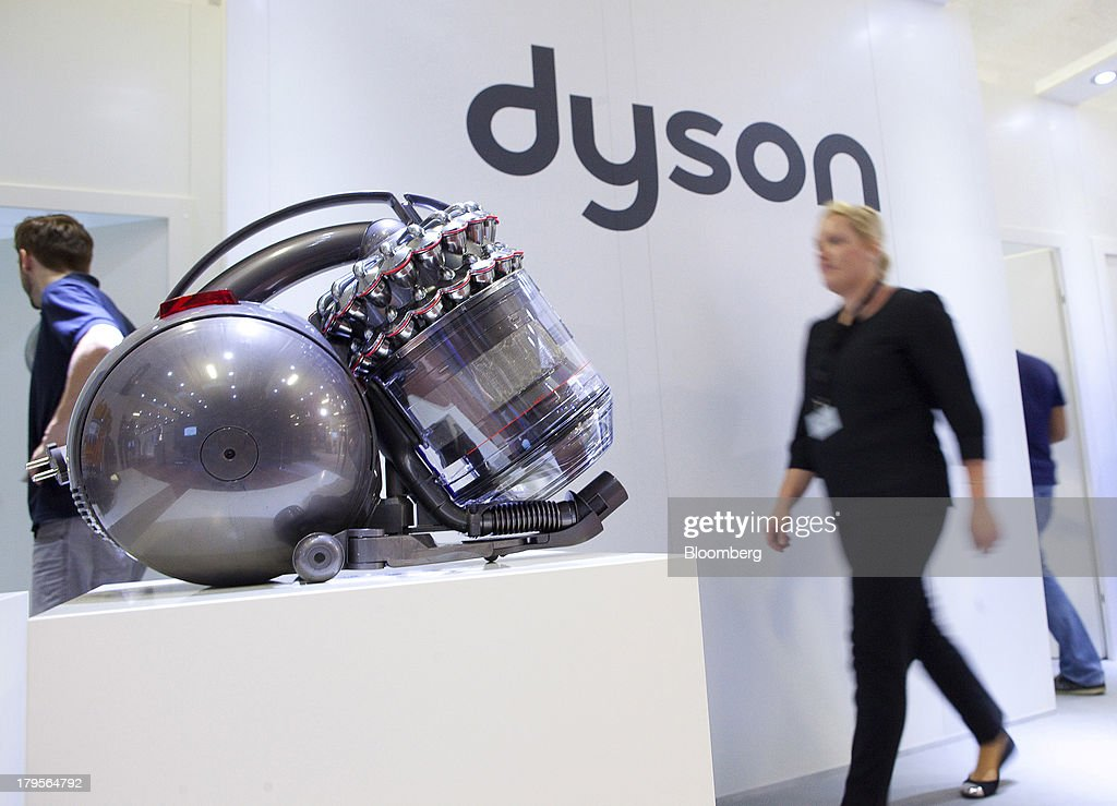 Employees pass a Dyson Cinetic DC 52 Animal Complete vacuum cleaner, manufactured by Dyson Ltd., displayed on the eve of the opening of the IFA consumer electronics show in Berlin, Germany, on Thursday, Sept. 5, 2013. Samsung showed the Galaxy Gear yesterday at IFA, Europe's largest consumer-electronics show, as it races Apple and Sony Corp. to carve a share of the market for wearable technology amid slowing growth in smartphones. Photographer: Krisztian Bocsi/Bloomberg via Getty Images