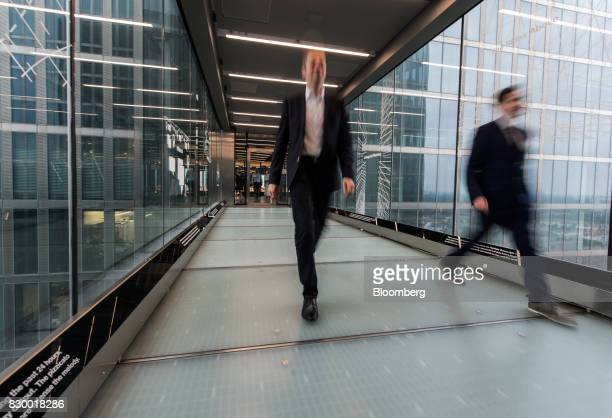 Employees pass along a connecting walkway at the International Business Machines Corp Watson cognitive computing platform Internet of Things center...