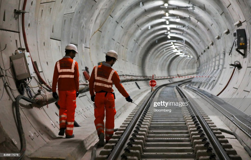 Employees pass along a section of Crossrail Ltd. track in a tunnel near Whitechapel station during an event to celebrate the completion of the permanent track on the Elizabeth line in London, U.K., on Thursday, Sept. 14, 2017. Crossrail, which will be known as the Elizabeth Line once its up and running, hasnt yet set fares, but transit agency Transport for London has indicated they will be significantly less than Heathrow Express with a charging structure more akin to the Tube. Photographer: Chris Ratcliffe/Bloomberg via Getty Images