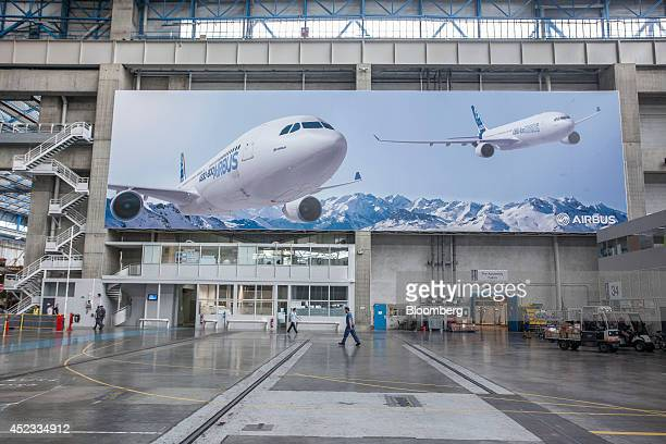 Employees pass beneath a banner showing Airbus A330 passenger jets in flight in the Airbus Group NV factory in Toulouse France on Friday July 18 2014...