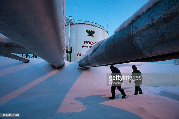 Employees pass beneath pipes leading to oil storage tanks at the central processing plant for oil and gas at the Salym Petroleum Development oil...