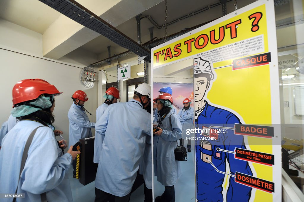 Employees pass by a board which mentions the security measures as they enter the Golfech nuclear power plant, southwestern France, on November 27, 2012. The slogan reads : 'Got everything ?'. CABANIS