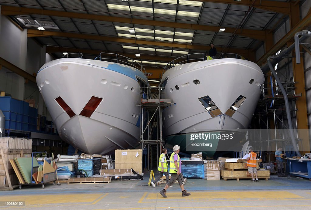 Employees pass the hulls of two 115 Sport Sunseeker yachts produced by Sunseeker International Ltd a unit of China's Dalian Wanda Group during...