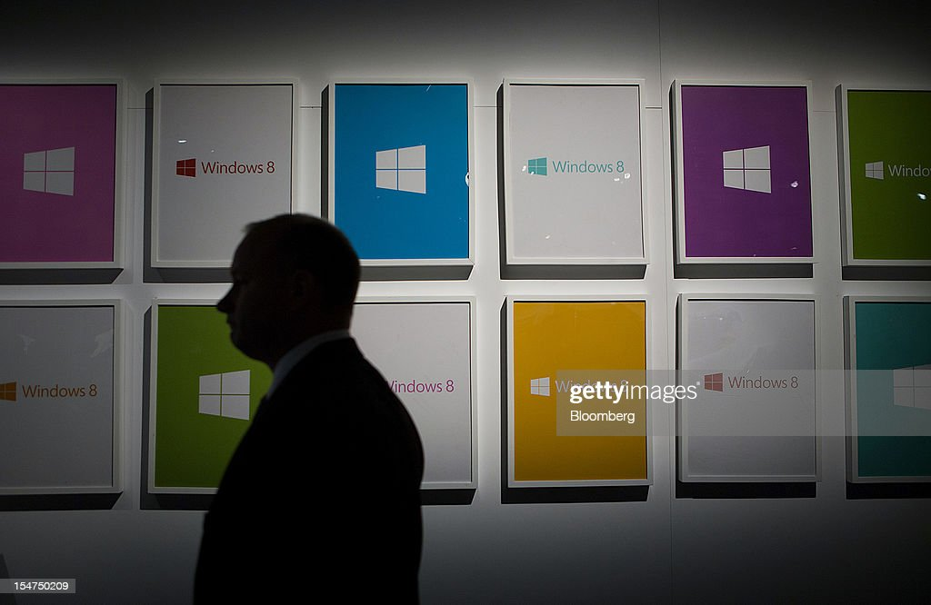 Employees pass the Microsoft Corp. Windows 8 logo during an event in New York, U.S., on Thursday, Oct. 25, 2012. Microsoft Corp. will be constrained in a contest against Apple Inc. in the market for handheld computers by unveiling a tablet that doesn't work with some of the most widely used downloadable applications. Photographer: Scott Eells/Bloomberg via Getty Images