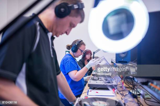 Employees perform an audio quality control check of vinyl records at the Precision Record Pressing facility in Burlington Ontario Canada on Friday...
