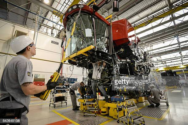 Employees place the carcass in a grain combine at CASE Combines assembly line Sorocaba Brazil on Wednesday September 18th 2013