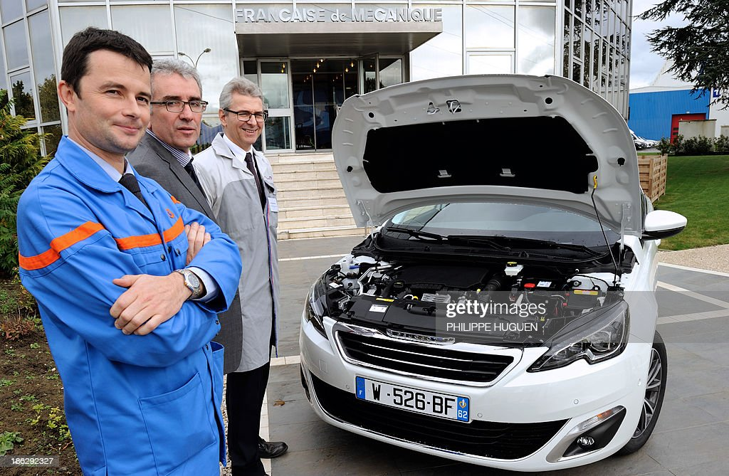 Employees pose in front of a new Peugeot 308 equipped with French carmaker PSA Peugeot Citroen's new engine, the three-cylinder EB Turbo 'Pure Tech', during the inauguration of an assembly line producing PSA's engine, on October 29, 2013 at the Francaise de Mecanique plant in Douvrin, northern France.