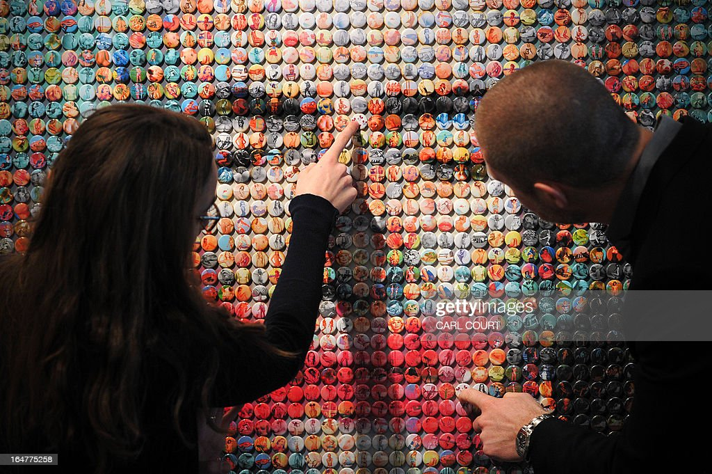 Employees pose in front of an art work depicting French former IMF chief Dominique Strauss-Kahn entitled 'La Pig' by British artist Joe Black at the Opera Gallery in central London on March 28, 2013. The work is made up of small badges showing pornographic images and photos of piglets and was created for French magazine Paris Match to celebrate its publication of 1001 covers since 1949.