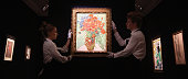 Employees pose with a painting by Vincent Van Gogh entitled 'Vase with Dasies and Poppies' during a press preview at Sotheby's on October 10 2014 in...
