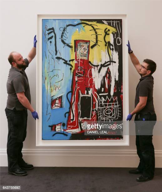 Employees pose with an artwork by US artist JeanMichel Basquiat 'untitled ' with an estimated price of 1418 million GBP during a photocall ahead of...