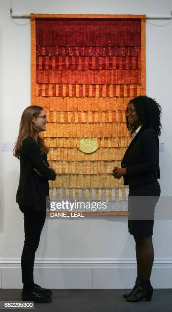 Employees pose with an artwork entitled 'Composition No 25 ' by Mali artist Abdoulaye Konate with an starting price of 1000015000 dollars /...