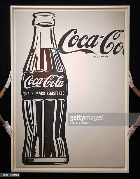 Employees pose with Andy Warhol's 'CocaCola [4] Large CocaCola' at Sotheby's auction house in London on October 11 2010 The painting forms part of...