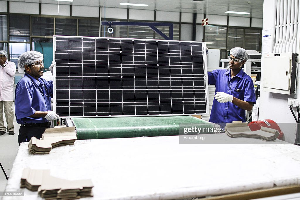 Employees prepare a solar panel for packaging at the Tata Power Solar Systems Ltd. manufacturing plant in Bangalore, India, on Tuesday, June 11, 2013. Tata Groups solar unit is expanding its business building plants for customers, forecasting that offices and factories will be paying more for grid power than solar by 2016 in most Indian states. Photographer: Dhiraj Singh/Bloomberg via Getty Images