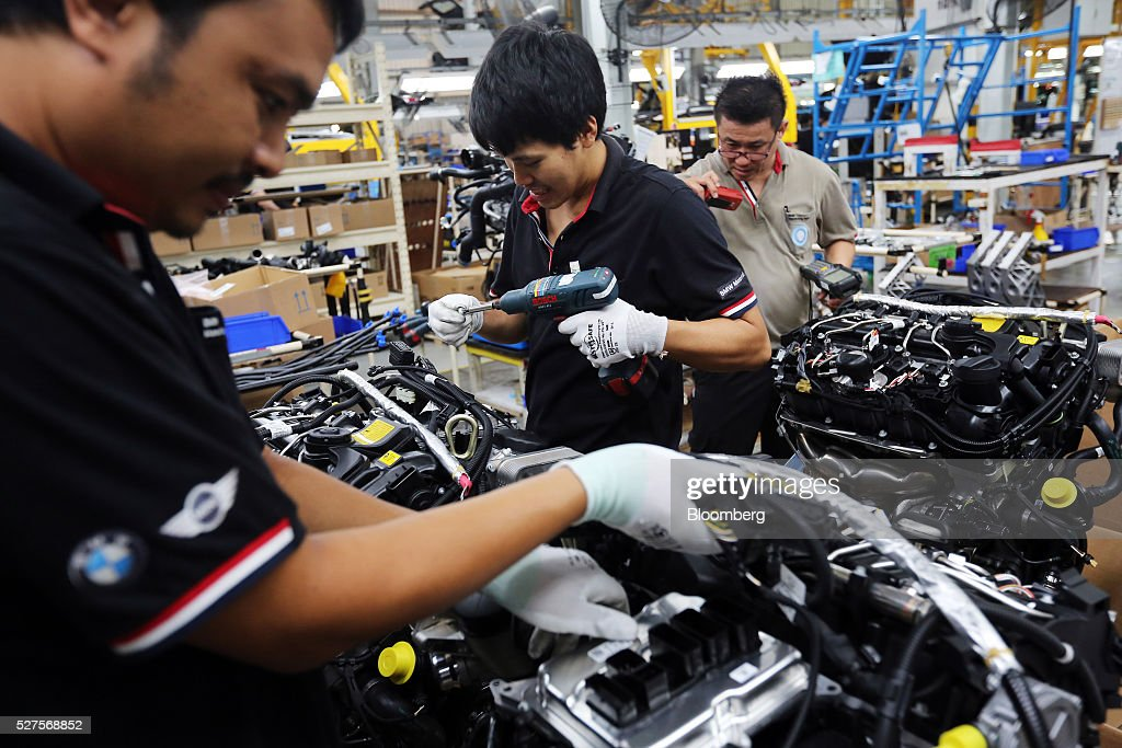 Employees prepare an engine for a BMW AG X3 vehicle at a BMW manufacturing plant in Pluak Daeng, Rayong Province, Thailand, on Tuesday, May 3, 2016. BMW's profit declined 2.5 percent in the first quarter on investment in new technologies like self-driving cars to defend its status as the world's biggest maker of luxury vehicles. Photographer: Dario Pignatelli/Bloomberg via Getty Images