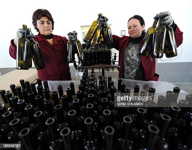 Employees prepare empty bottles at a winery in the Georgia's village of Patardzeuli some 30 km east of the capital Tbilisi on October 21 2013 AFP...