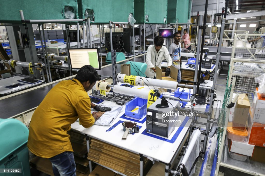 Employees prepare packages for shipment at the Amazon.com Inc. fulfillment center in Hyderabad, India on Thursday, Sept. 7, 2017. Amazon opened its largest Indian fulfillment center in Hyderabad. The center spans 400,000 square feet with 2.1m cubic feet of storage capacity the company said in a statement. Photographer: Dhiraj Singh/Bloomberg via Getty Images