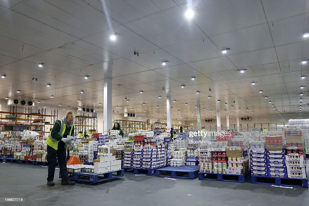 Employees prepare pallets with produce ahead of transporting to stores inside WM Morrison Supermarkets Plc's distribution center in Wakefield, U.K., on Thursday, Nov. 22, 2012. Britain's economy will return to growth next year after stagnating in 2012, with expansion weighted in the second half, according to Bank of England projections published yesterday. Photographer: Simon Dawson/Bloomberg via Getty Images