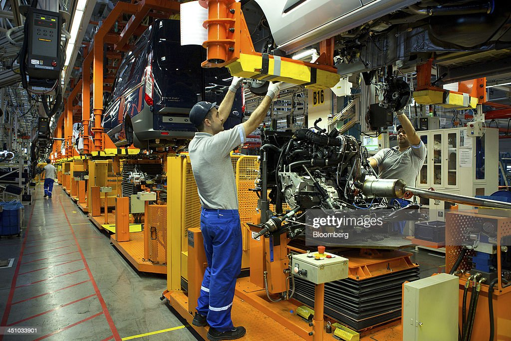 Employees prepare to fit a pre-assembled engine to the body of a Ford Transit van as it moves along the production line at the Ford Otosan plant, the joint venture between Ford Motor Co.'s Ford Otomotiv Sanayi AS and Koc Holding AS, in Golcuk, Turkey, on Wednesday, Nov. 20, 2013. Istanbul-based Automobile Distributors' Association, or ODD, forecasts Turkey's total automotive industry market to be between 830k and 870k this year. Photographer: Kerem Uzel/Bloomberg via Getty Images