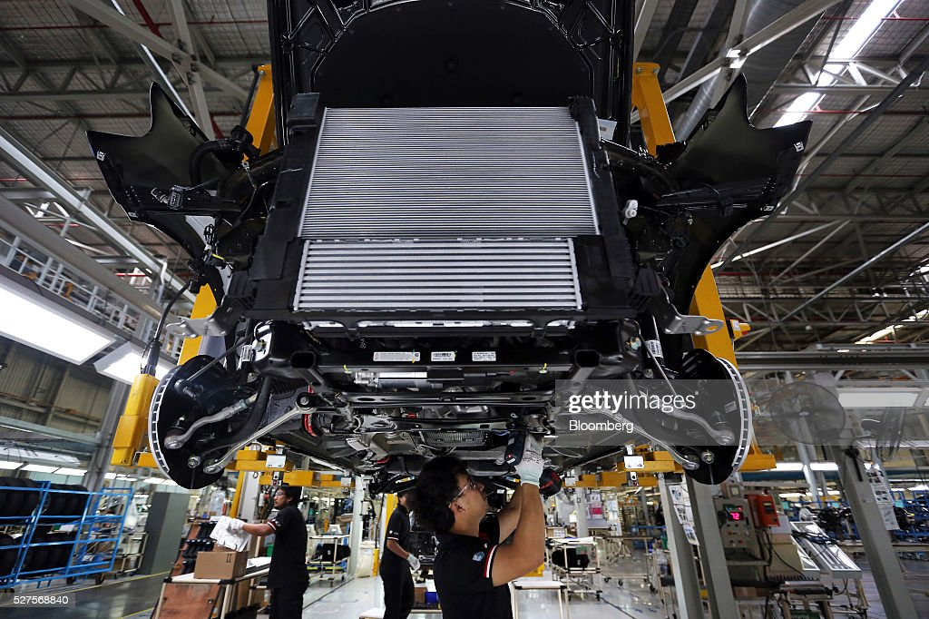 Employees prepare to mount an engine on a BMW AG X3 vehicle at a BMW manufacturing plant in Pluak Daeng, Rayong Province, Thailand, on Tuesday, May 3, 2016. BMW's profit declined 2.5 percent in the first quarter on investment in new technologies like self-driving cars to defend its status as the world's biggest maker of luxury vehicles. Photographer: Dario Pignatelli/Bloomberg via Getty Images