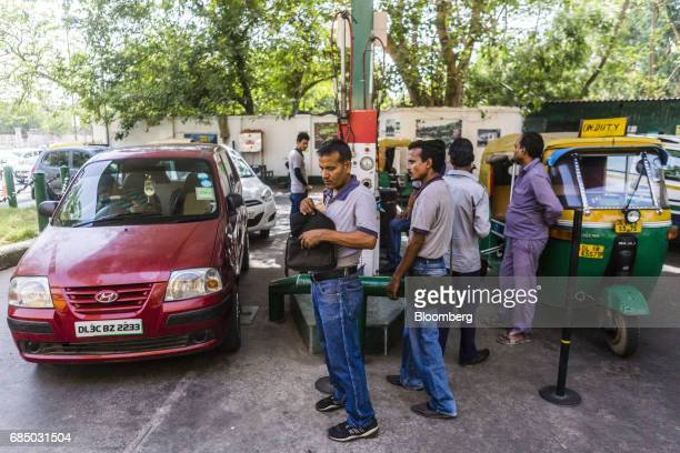 Employees prepare to refuel vehicles with compressed natural gas at an Indraprastha Gas Ltd gas station in New Delhi India on Wednesday May 17 2017...