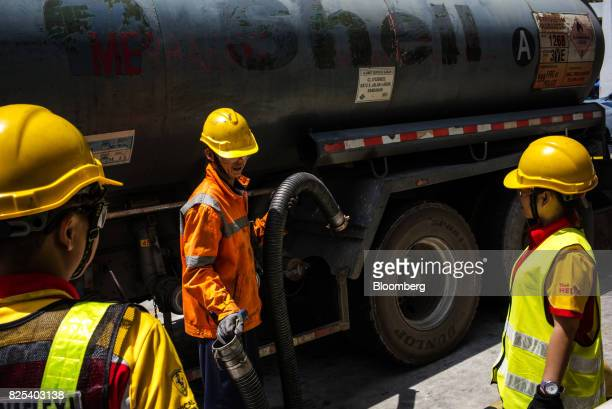 Employees prepare to tranfer fuel from a tanker truck to gas fuel tanks at a Royal Dutch Shell Plc gas station in Kota Kinabalu in Sabah Malaysia on...