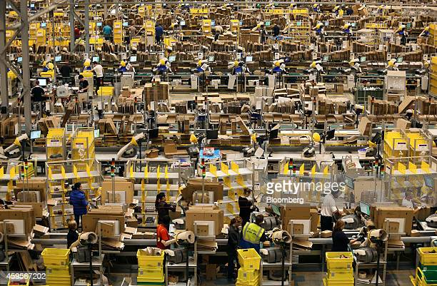Employees process customer orders ahead of shipping at one of Amazoncom Inc's fulfillment centers in Peterborough UK on Tuesday Nov 25 2014 Online...