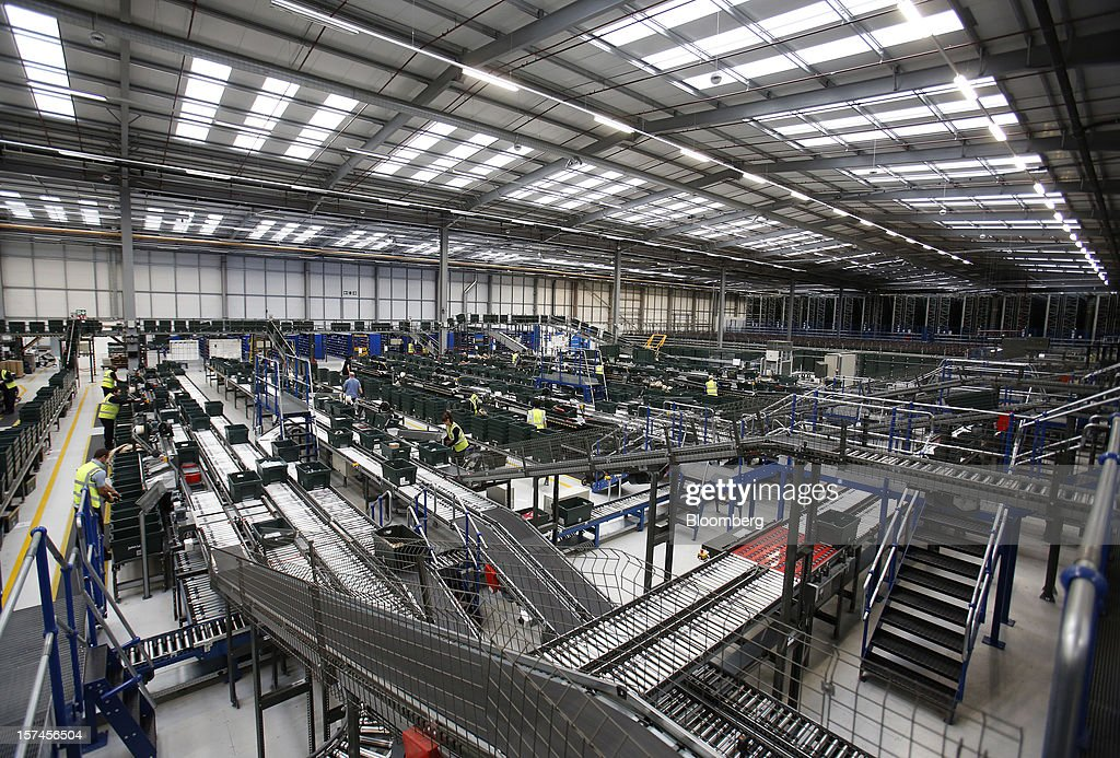 Employees process customers' orders as inside the John Lewis Plc semi-automated distribution centre in Milton Keynes, U.K., on Monday, Dec. 3, 2012. An index of U.K. retail sales rose to a five-month high in November, according to a monthly report from the Confederation of British Industry. Photographer: Simon Dawson/Bloomberg via Getty Images